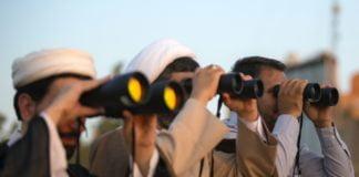 three men using binoculars