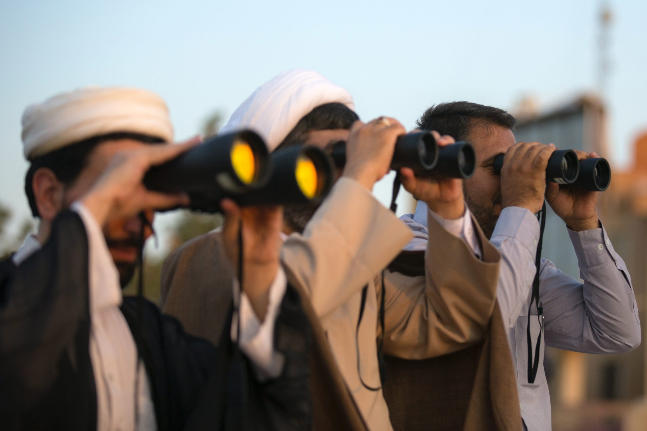 three men using binoculars